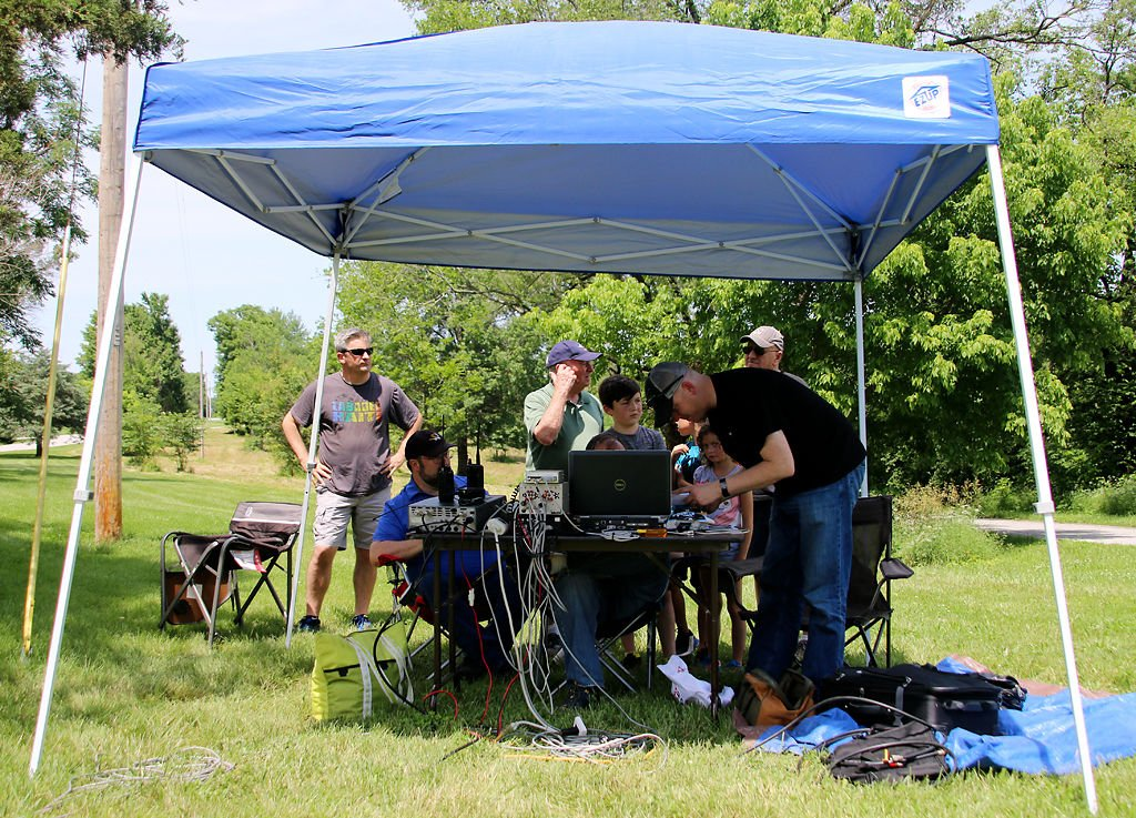 Visitors gather around satellite-monitoring equipment at an amateur radio field day exercise