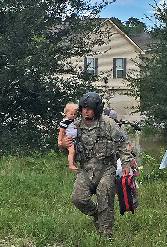 Chad McCann brings a young child to the waiting UH-60 Blackhawk