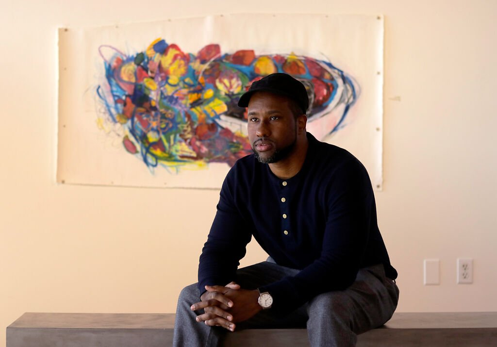 Askia Bilal sits in front of his piece
