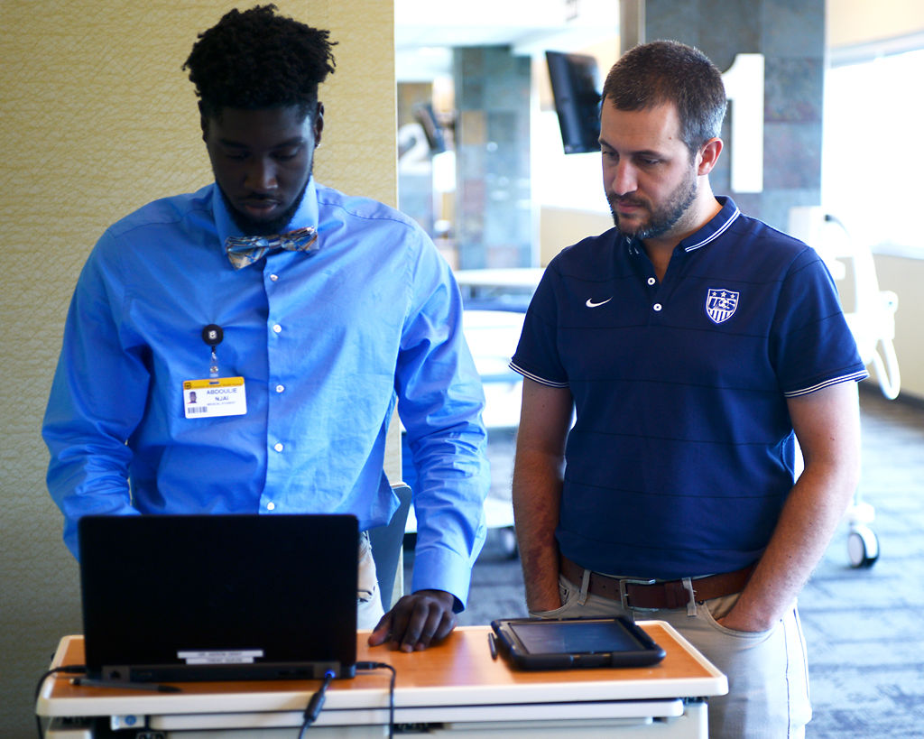 Medical student Abdoulie Njai, left, and Dr. Aaron Gray look at joint analysis results
