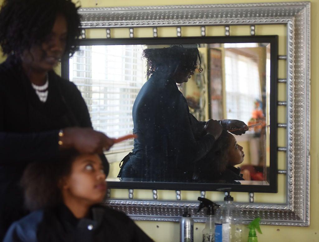 Haby Boukari combs through Angelique Twagirayezu's hair