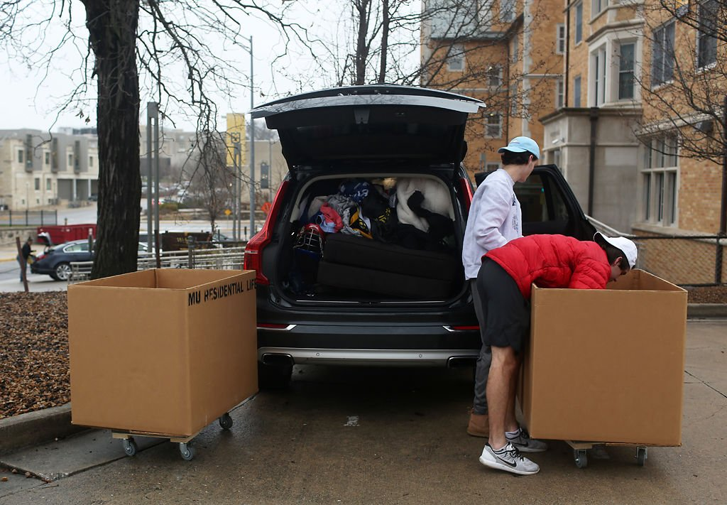 Patrick Smith, right, and his younger brother Brendan Smith unload boxes