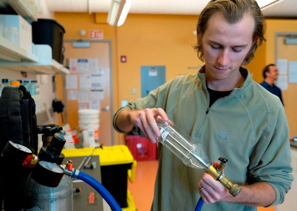 Matthew Ashby assembles a spraying backpack
