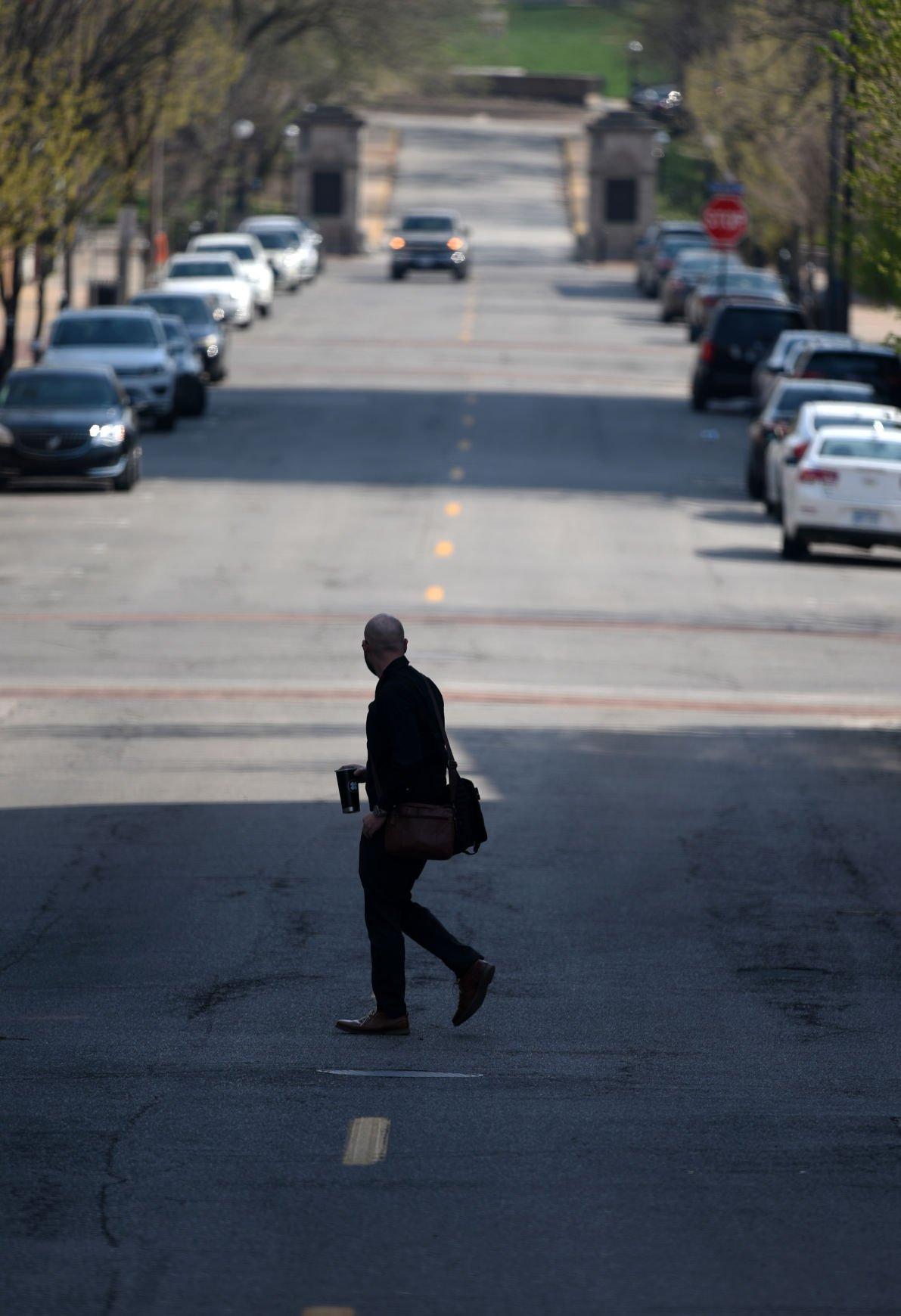 A man crosses 8th Street