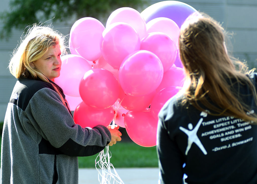 Cheyenne Curry holds a bundle of balloons Friday at Battle High School in Columbia. I