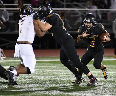 Hickman High School offensive lineman Ryan Upham blocks Battle High School's De'Shannon Turner