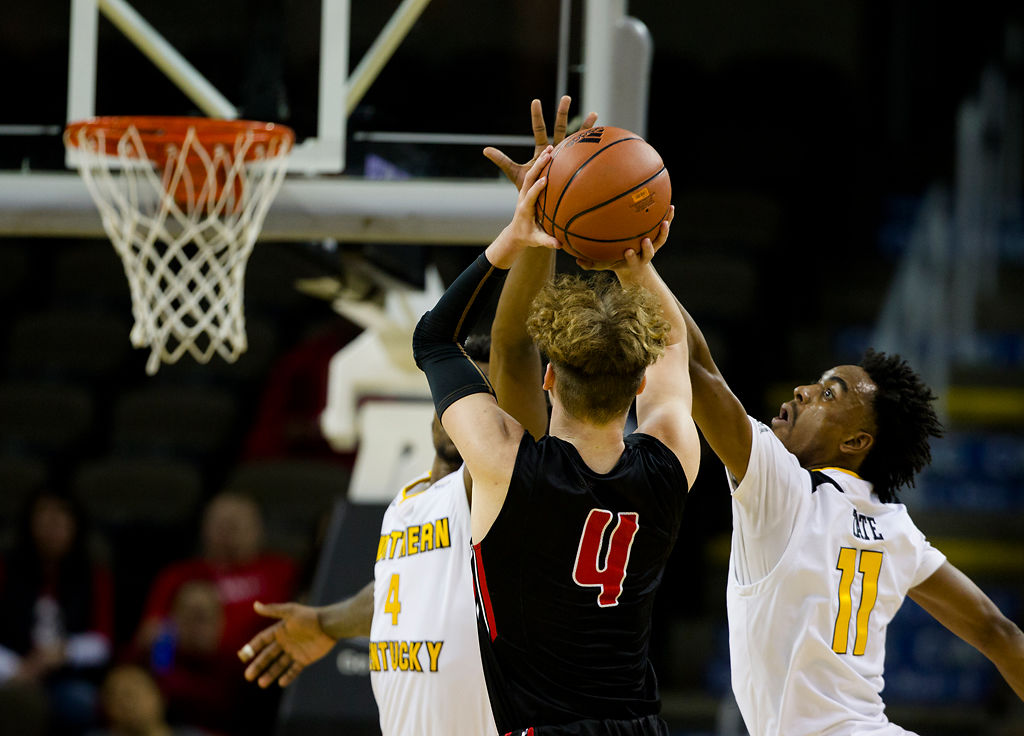 Northern Kentucky guard Jalen Tate (11) attempts to block the shot of Cincinnati-Clermont guard Noah Pedelty (4) during the first half of an NCAA college basketball game Tuesday, Nov. 5, 2019, in Highland Heights, Ky. (Albert Cesare./The Cincinnati Enquirer via AP)