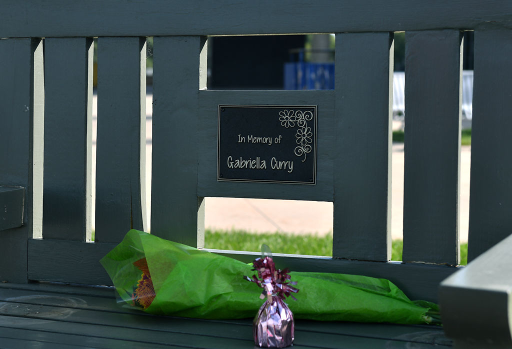 Flowers and a balloon weight sit on Gabriella Curry's memorial bench Friday at Battle High School in Columbia.