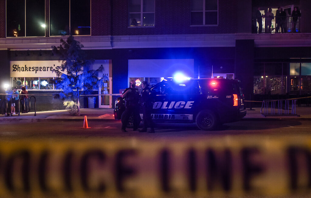Columbia police officers discuss at the crime scene of a shooting