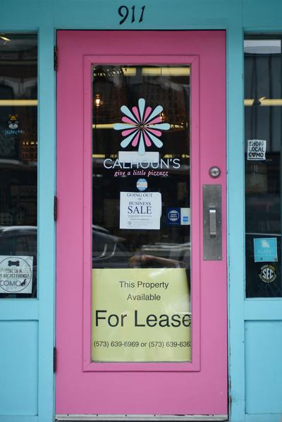 For sale and available-for-lease signs hang on the door of Calhoun's