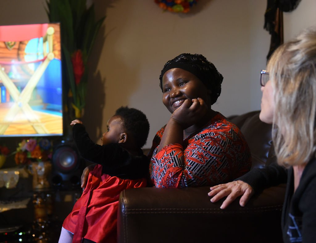 Bukuru Nihabose, center, talks to Samantha Christian in her new apartment