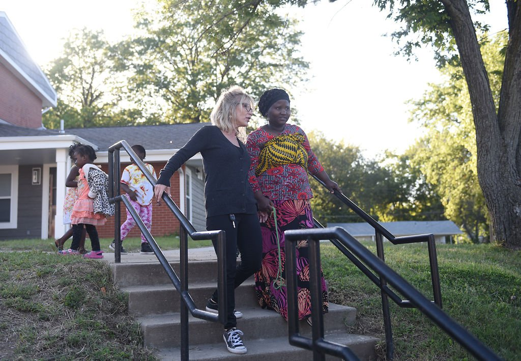 Samantha Christian, left, and Bukuru Nihabose look at the dedication ceremony for Bryant Walkway Apartments