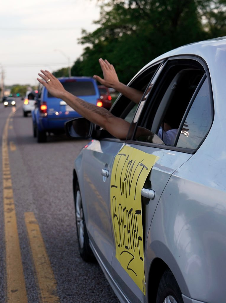 Dominic Perrigo sticks his hands out the window from his car during a 'hands up, don't shoot!' chant