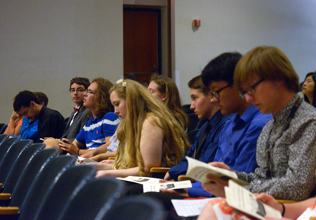 Seven middle school and high school student composers sit near the stage