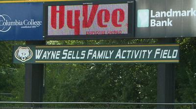 "The ""Wayne Sells Family Activity Field"" sign hangs below the scoreboard on Wednesday at Rock Bridge High School."