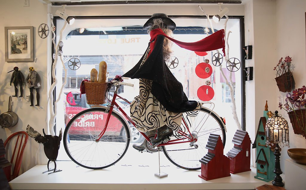 A sculpture of a woman riding a bike is set up in the main display window