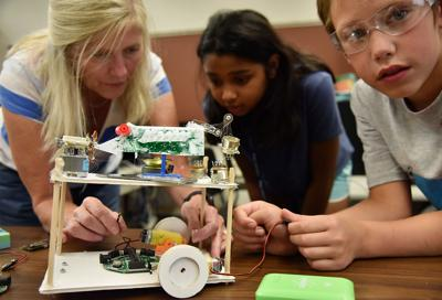 Julie Nichols, Shreeyanka Bardhan, 10, and Dakota Johnson, 9, work on placing wires