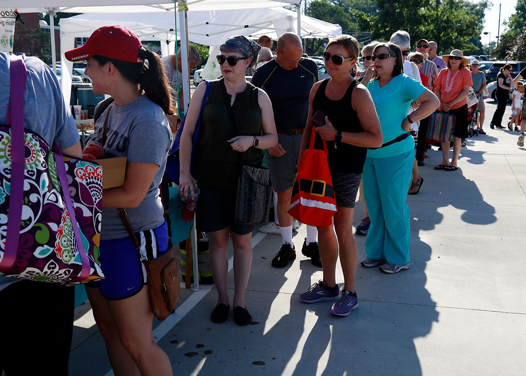 Customers wait in line to buy produce at the Columbia Farmers Market
