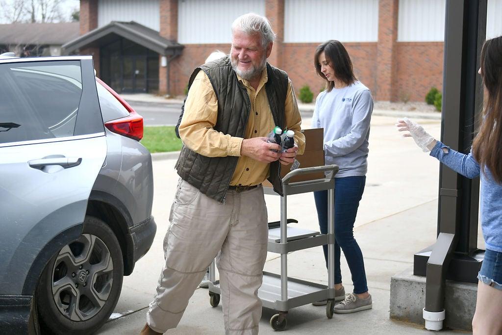 Jim Abernathy, left, picks up communion