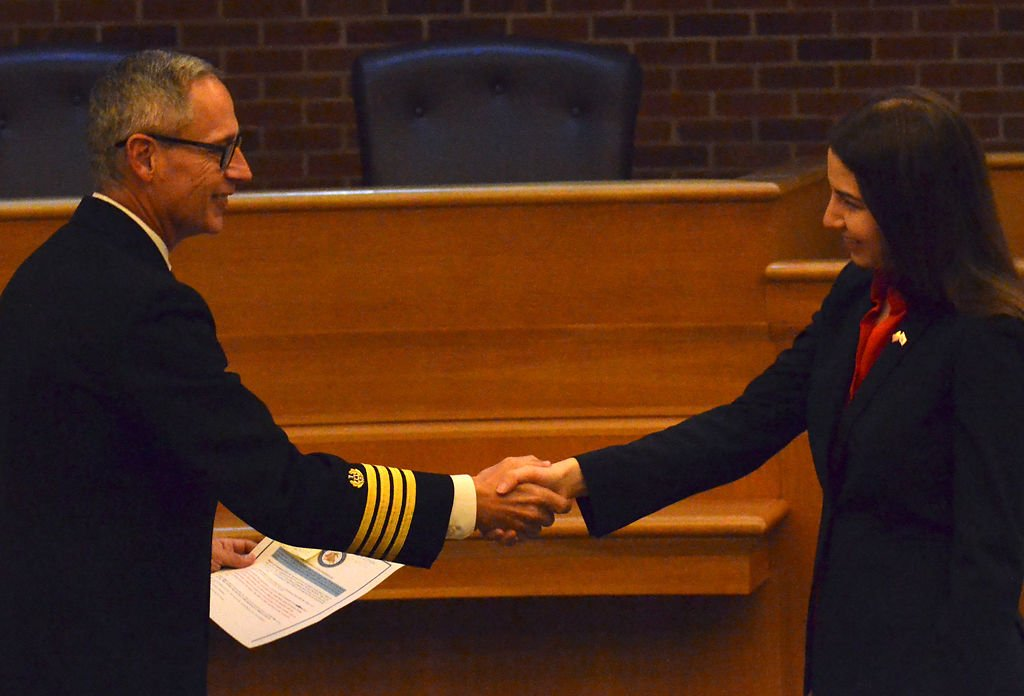 Professor Brent Filbert, a retired Captain of the U.S. Navy, shakes hands with Larissa Tiller