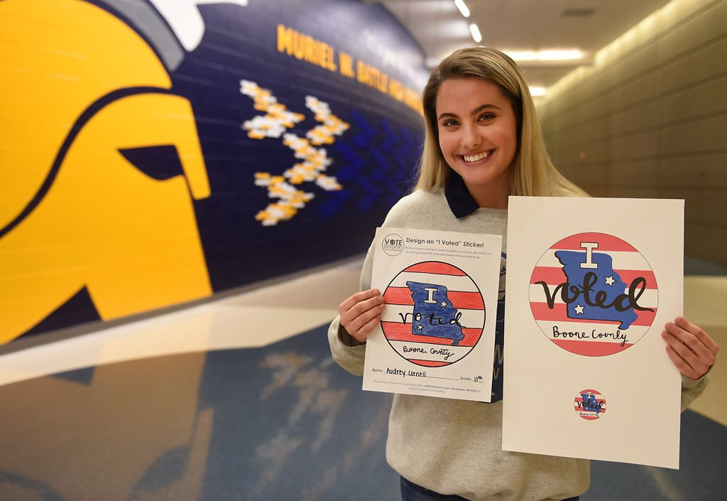 """Audrey Cornell poses for pictures and holds up her art after winning the """"I voted"""" sticker contest"""
