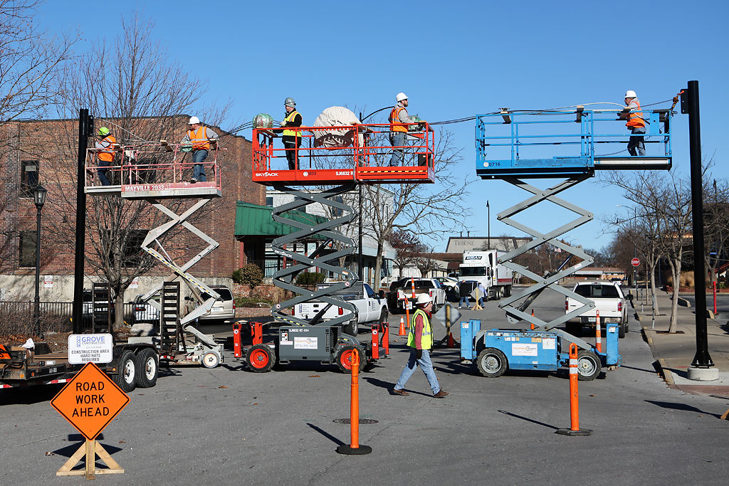 Construction workers install artwork above Fourth Street