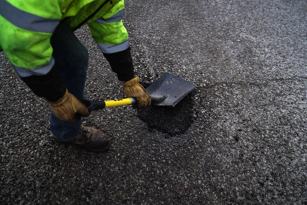 Missouri Department of Transportation employee Scott Quint fills a pothole