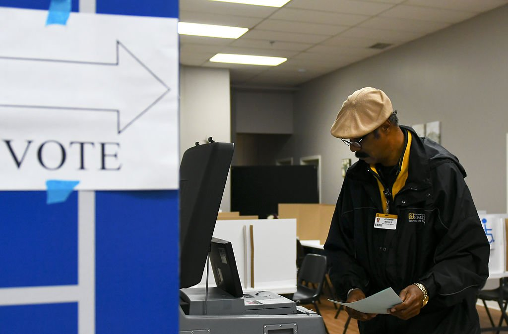 Johnnie Wells turns in his ballot to place his vote in the democratic primary