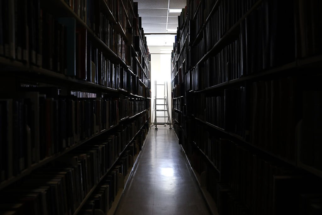 A ladder sits unused at the end of an aisle of books at Ellis Library