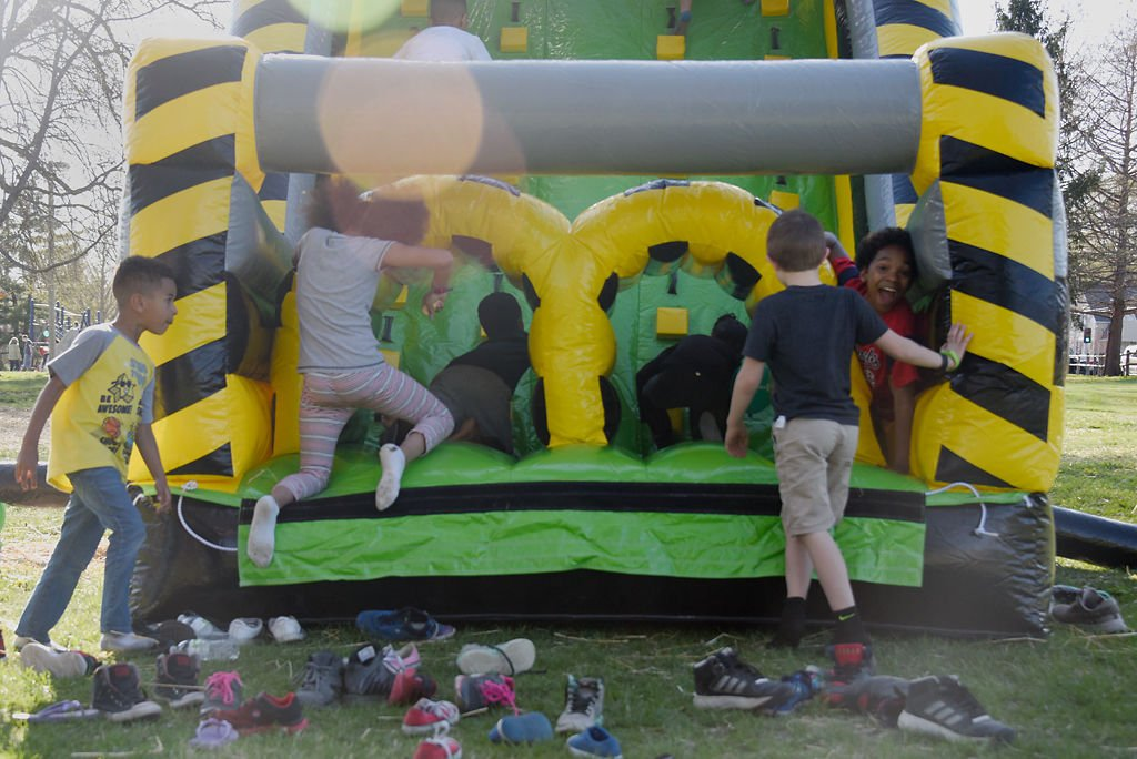 Children take off their shoes and jump into an inflatable bounce house