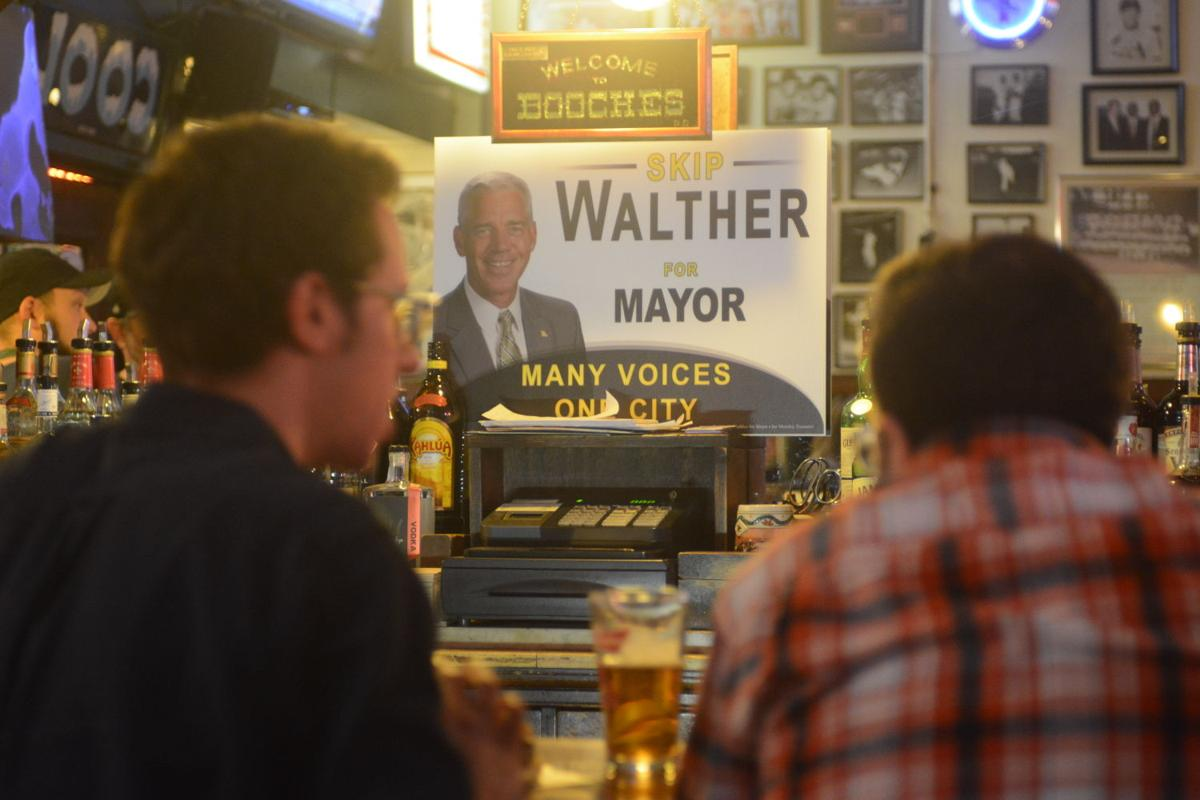 Two men enjoy a drink at Skip Walther's fundraiser
