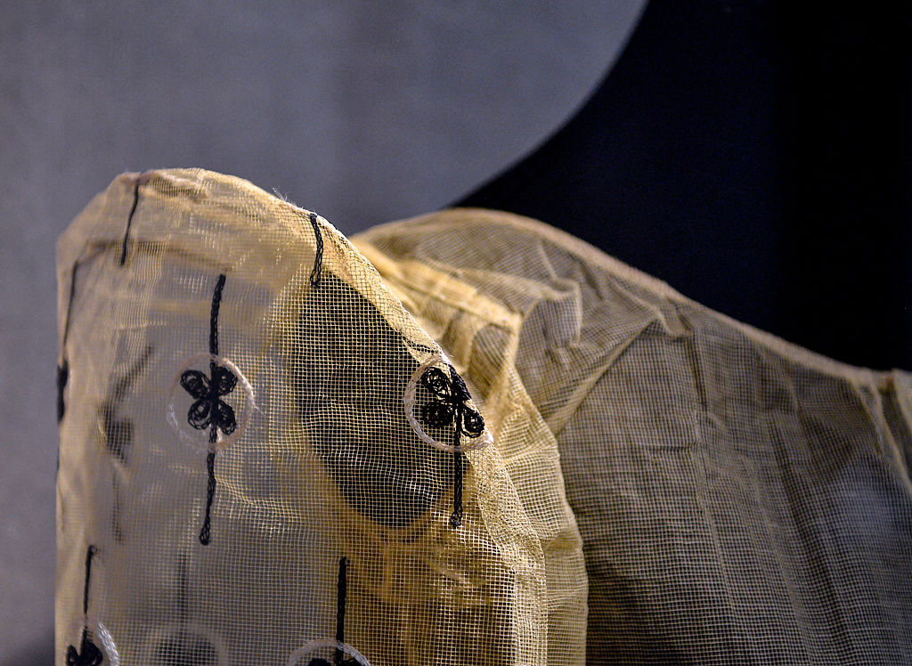 A garment made from pineapple leaves sits behind glass