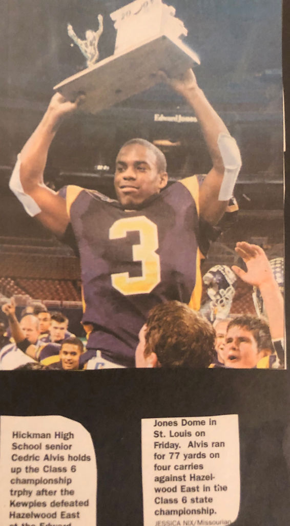 A newspaper clipping of Cedric Alvis holding up the Class 6 championship trophy