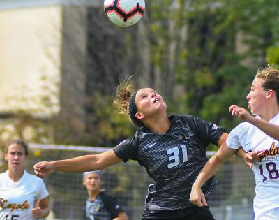 Madison Lewis heads a ball