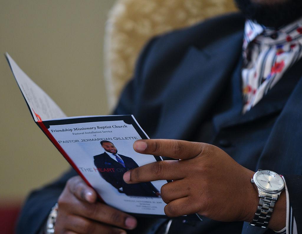 Pastor Jermareian Gillette reviews a program for the service