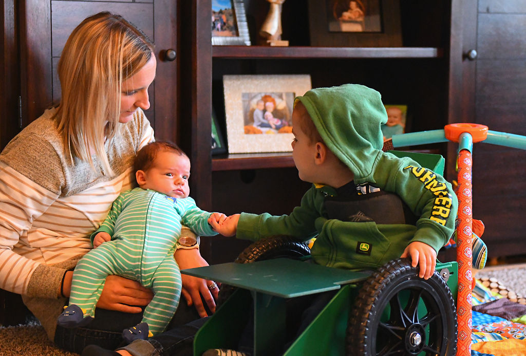 Brody Moreland, 2, reaches out for his month-old baby brother