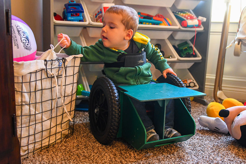 Brody Moreland, 2, reaches for his toys while in his Go Bro, a wheelchair his parents designed for him