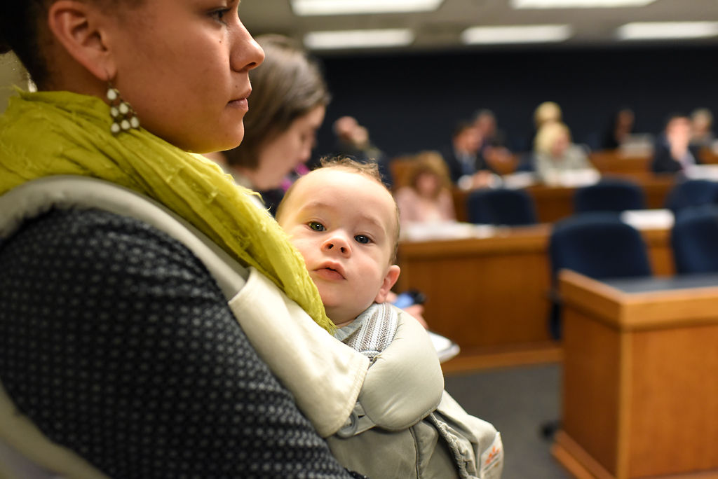 Jessica Mathenia and her daughter Kyrie Mathenia, 7 months, sit in on a debate about abortion