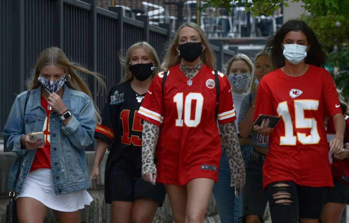 A group of young adults walks down Ninth Street wearing Chiefs jerseys