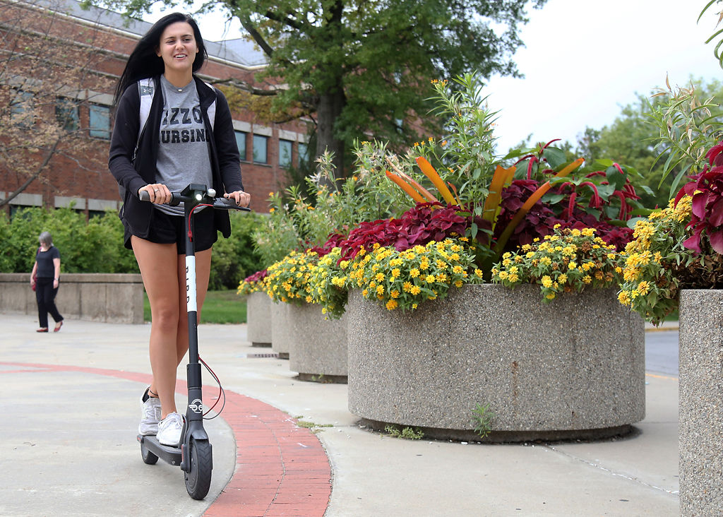 Allie Mabley, an MU student, rides a Bird scooter through MU's Speakers Circle