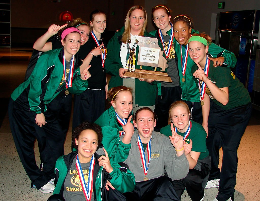 The 2008 Rock Bridge Women's basketball team holding up No. 1 fingers and pose with the trophy.