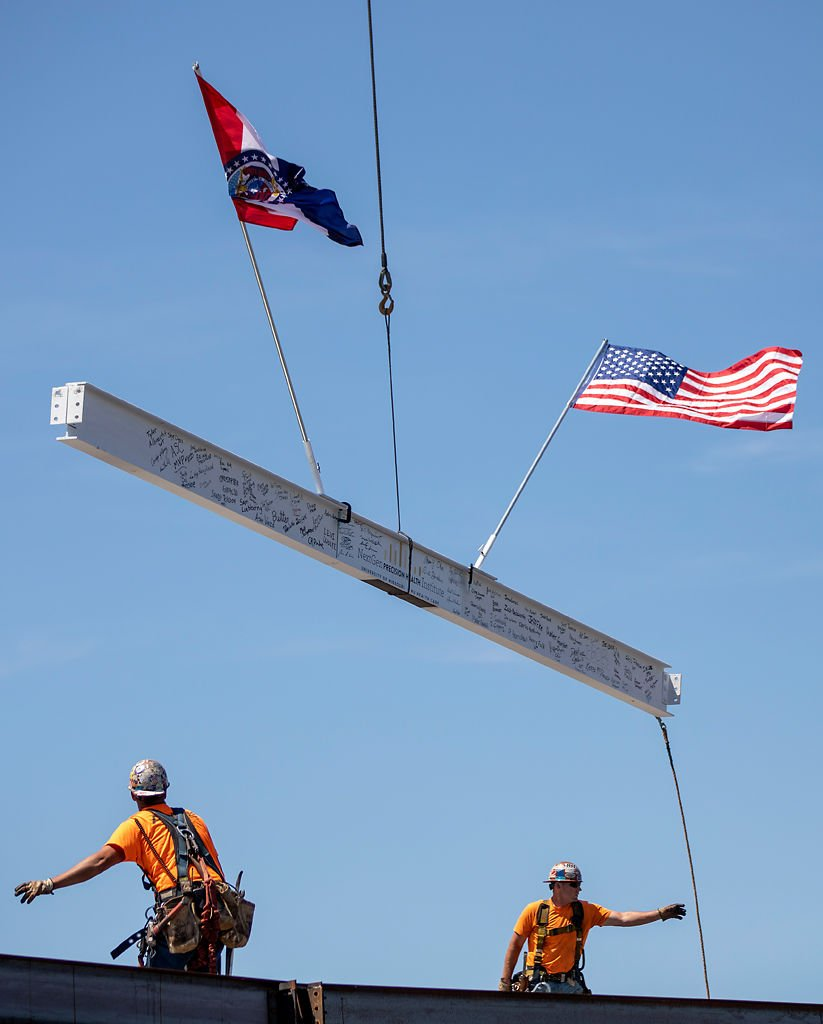 Workers place I-beam for NextGen Precision Health Institute