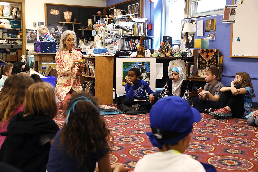 Third grade students listen to art teacher Gennie Pfannenstiel