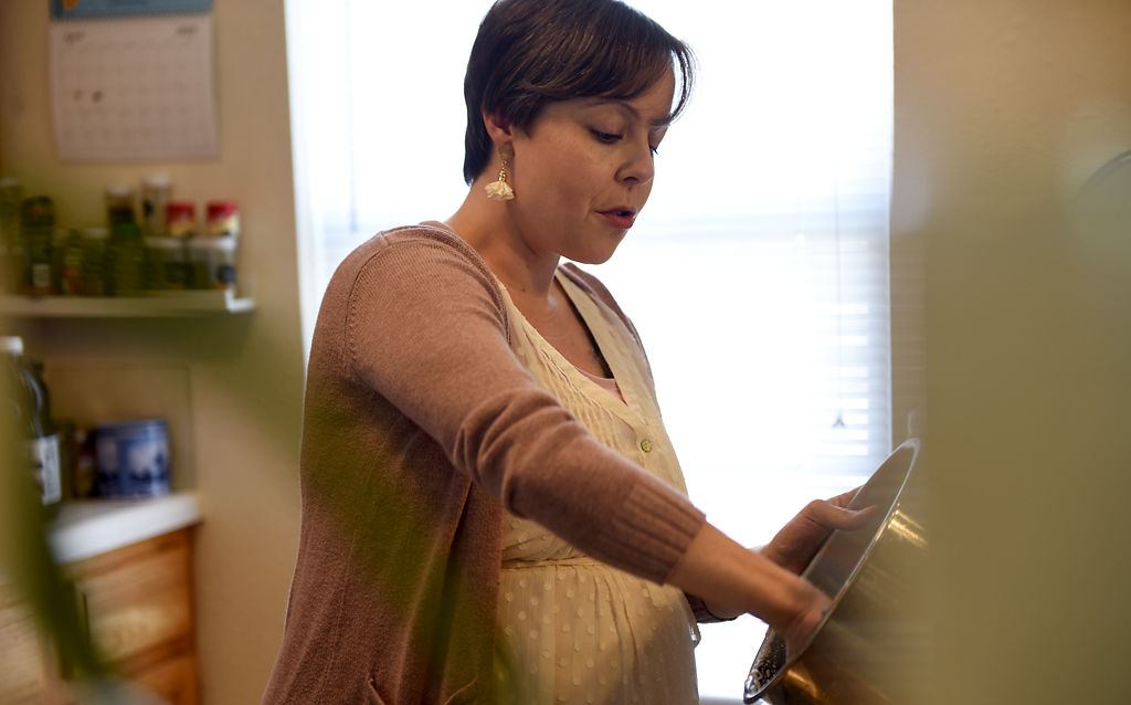Expectant mother Rachel Long washes dishes in her kitchen