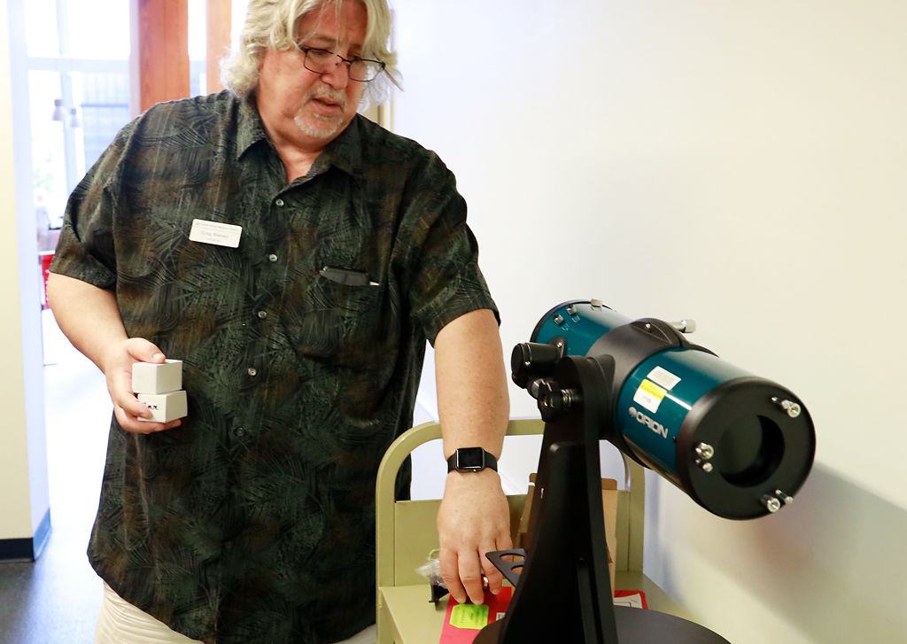 Greg Reeves demonstrates the new telescopes that the library has available for checkout