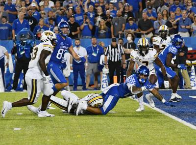 Kentucky's Chris Rodriguez Jr. eyes the ball as he is tackled by Jaylon Carlies (copy)