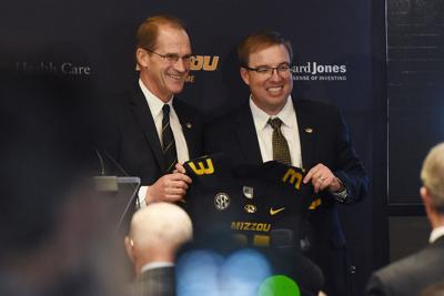 Jim Sterk Eliah Drinkwitz pose for a photo with a football jersey