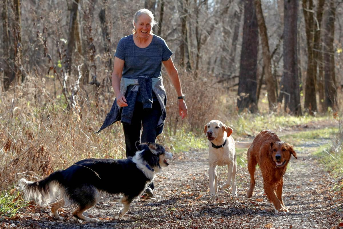 Debbie Heifner walks with her dogs Rango, Fizzle and Spur through the woods