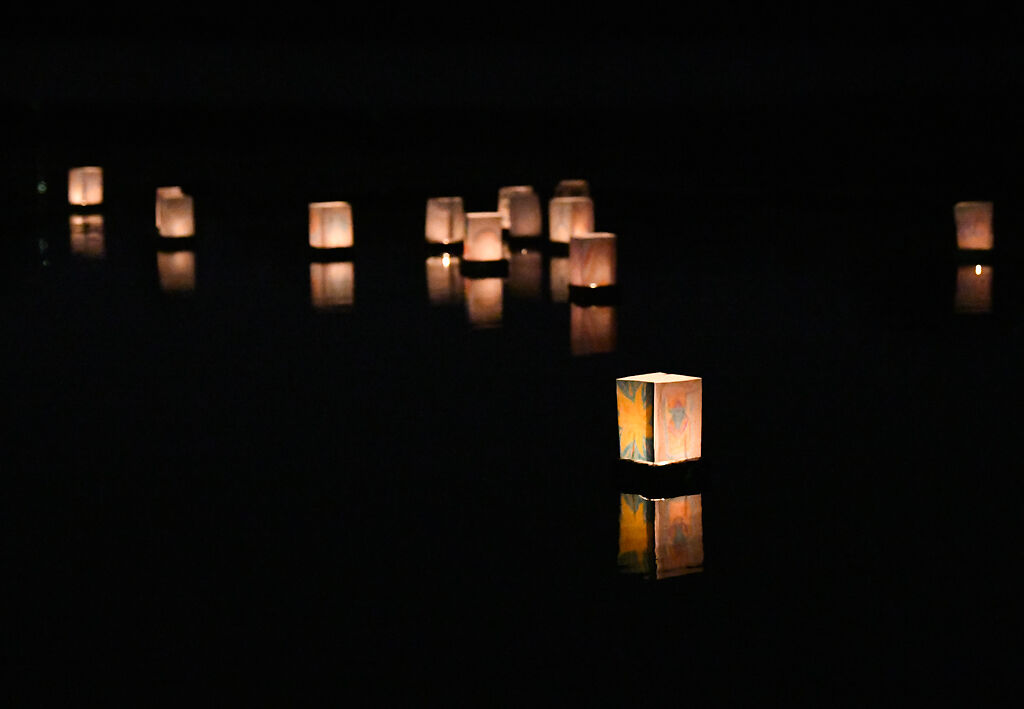 Floating lanterns drift away from the shore