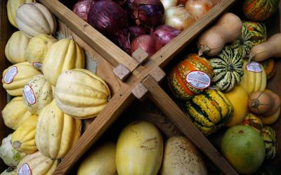 Fresh vegetables rest in a wooden display